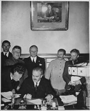 Molotov signs the Molotov-Ribbentrop Pact in Moscow. Behind him are Shaposhnikov, Ribbentrop, and Stalin.