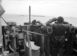 Officers on the bridge of a destroyer on convoy escort duties keep a sharp look out for enemy submarines during the Battle of the Atlantic, October 1941