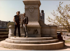 "Activist Michael K at the statueless pedestal of the controversial police monument in the remains of Chicago's Haymarket Square on the tragedy's 100th anniversary in early May, 1986. He reportedly ""took to his grave"" whatever he knew about the 1969 and 1970 bombings (the pedestal has since been removed)."