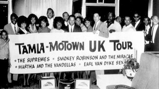 "A posed photograph from Motown's landmark 1965 tour of the United Kingdom. Third from left is Florence Ballard of The Supremes; to her left are her bandmates Diana Ross, Mary Wilson, Miracles member Bobby Rogers, Martha Reeves of Martha & the Vandellas, Ronnie White of The Miracles, Motown chief Berry Gordy, Jr., Vandellas Rosalind Ashford and Gloria Willaimson, and, holding up the sign directly above the ""UK"", Miracles lead singer Smokey Robinson."